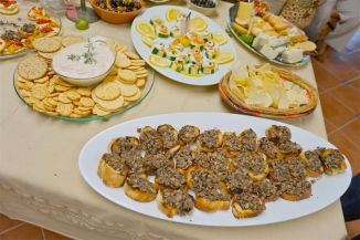 Lower right, crowded and ungranished, Mushroom duxelles on grilled crostini, middle left, smoked salmon spread, large whit platter, cucumber cups stuffed with  cream cheese, smoked salmon flags and a caper, crowded cheese plate.