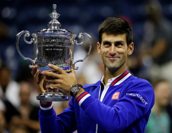 Novak Djokovic, of Serbia, holds up the championship trophy after beating Roger Federer, of Switzerland, in the men's championship match of the U.S. Open tennis tournament, Sunday, Sept. 13, 2015, in New York. (AP Photo/David Goldman)